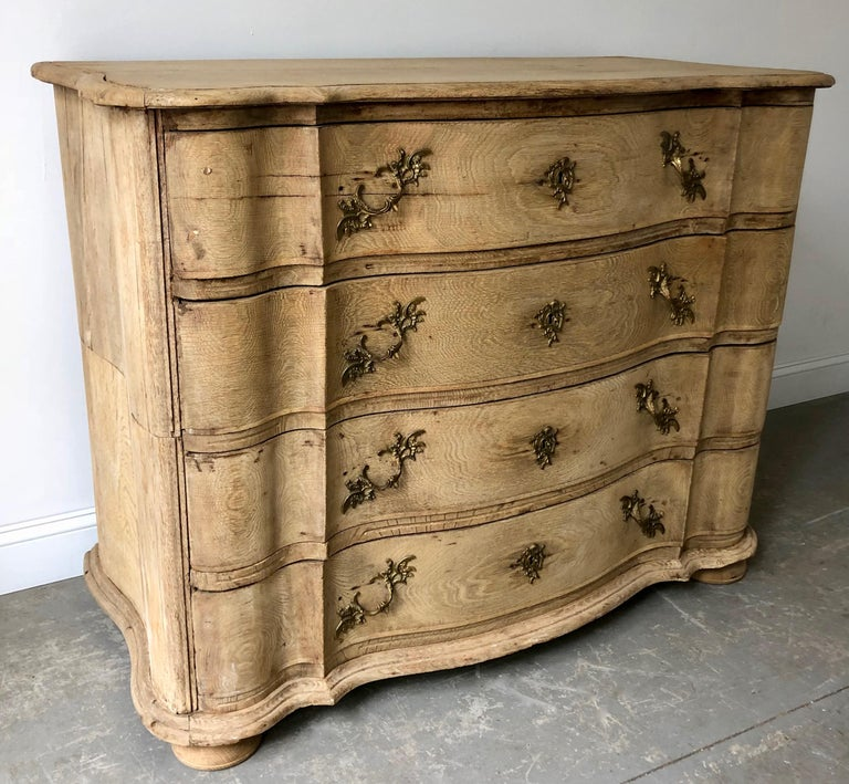 19th century chest of drawers in richly carved bleached oak with curvaceous serpentine drawer fronts, handsome bronze hardwares and shaped top on bun feet. The chest is in two parts for convent travels. Denmark, circa 1850. More than ever, we
