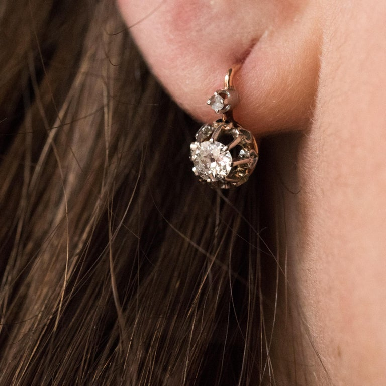 For pierced ears. Earrings in 18 karat rose gold. Pair of lever- back earrings, each is set with claws fleur de lysées of an antique brilliant- cut diamond, surmounted by a rose- cut diamond. The hooking system is from the back. Height: 12.9 mm,