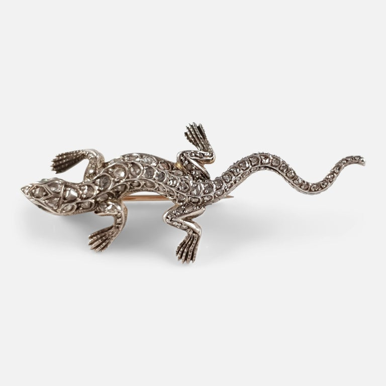 Description: - A stunning antique silver and rose gold diamond, and emerald lizard brooch - circa 1895. The brooch is crafted in silver to the front and backed in gold, with rose-cut emerald eyes, an engraved head, body, and tail that is highlighted