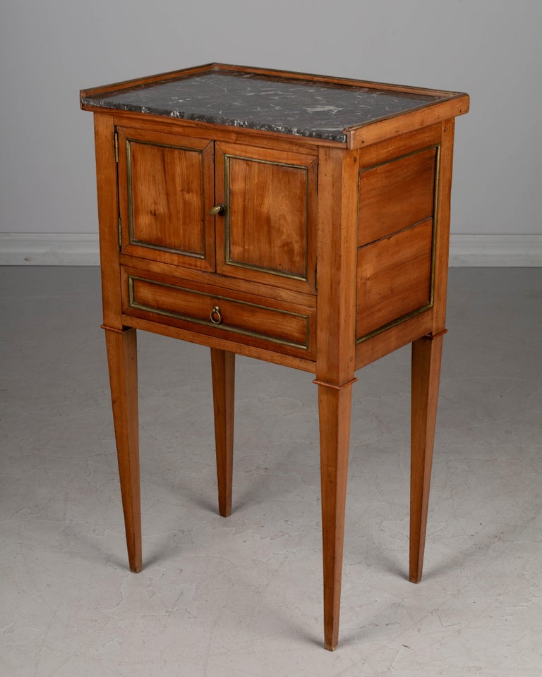 19th century Directoire style French side table, or nightstand, made of solid cherrywood with brass trim and original St. Anne gray marble top. An unusual cabinet with two doors above a dovetailed drawer. Sturdy and well-crafted using pegged