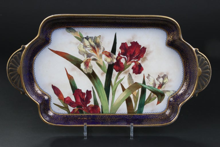 Lovely Doulton Burslem, England, hand painted dessert set: 1 rectangular tray and 8 small square plates. Depicts red and white irises and primroses, surrounded by a cobalt blue and gold border. Each item is hand painted with a different design. This