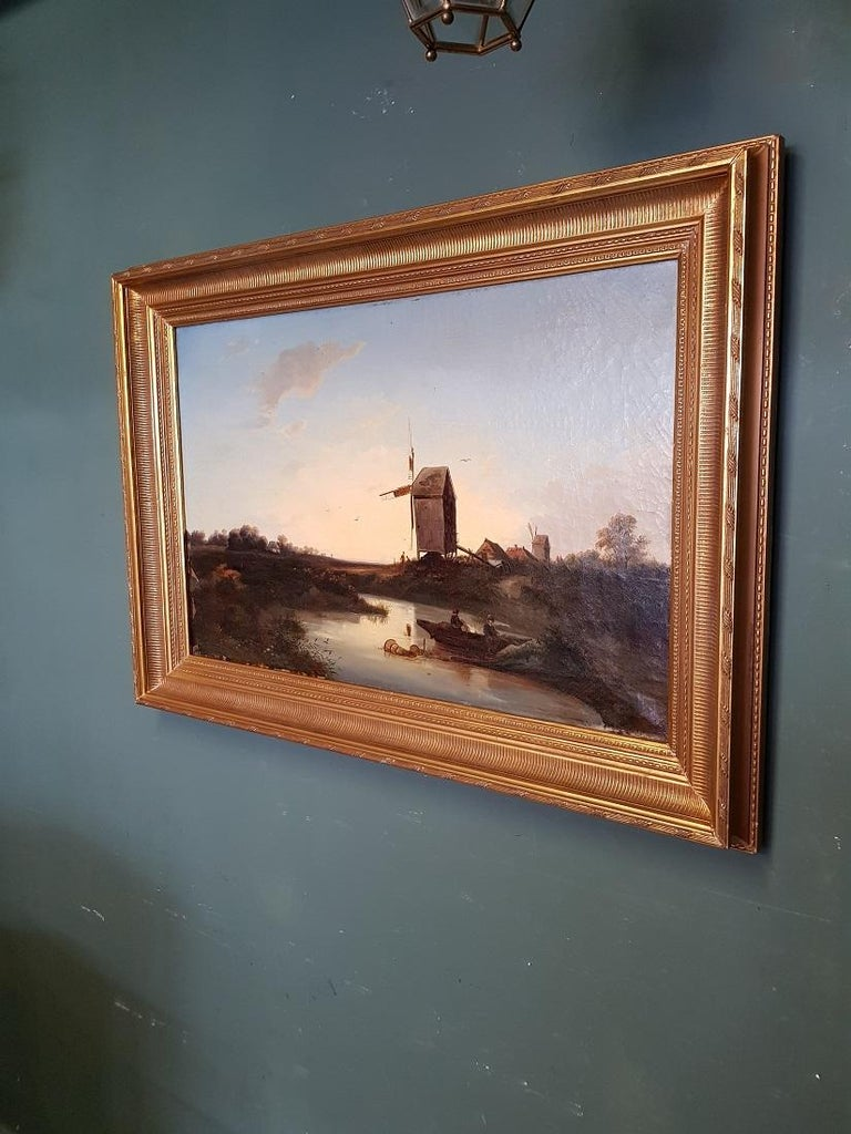 Antique Dutch School oil painting on canvas with polder landscape of fishermen near a mill in a new gilt frame (with some little wear), it has some paint loss in the left corner and around crackle further in a reasonable condition. Originating from