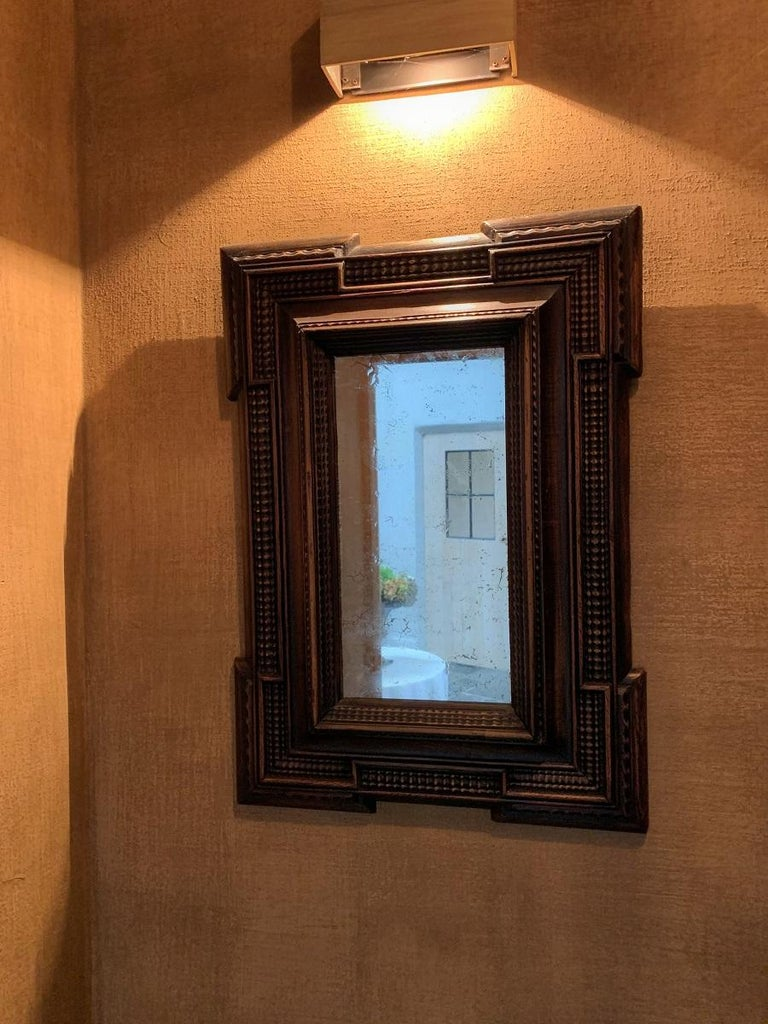 A 19th century ebonized Italian mirror in classical 17th century style. Made from softwood, finely moulded and decorated. Original mirror, soft patina.