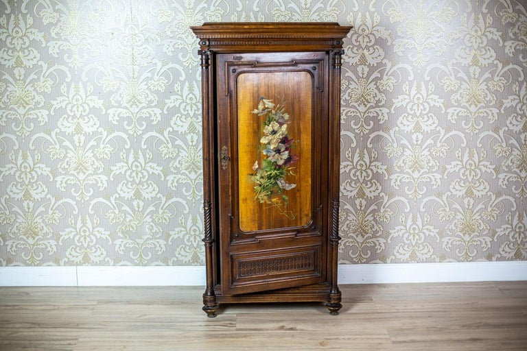 We present you this small, single-leaf chest piece of furniture, topped with a straight cornice. The door leaf is flanked by columns. Furthermore, the door panel is painted with a floral motif. The inside is divided by three shelves.  This