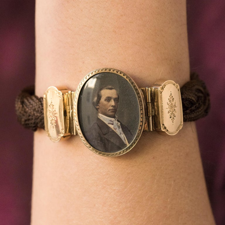 Antique bracelet, it is made of braided brown hair. The hinged clasp is in 18 karats yellow gold, carved with floral motifs and carry, in the center, a closed set recolored photograph. It represents an elegant delicately realized. Height at the