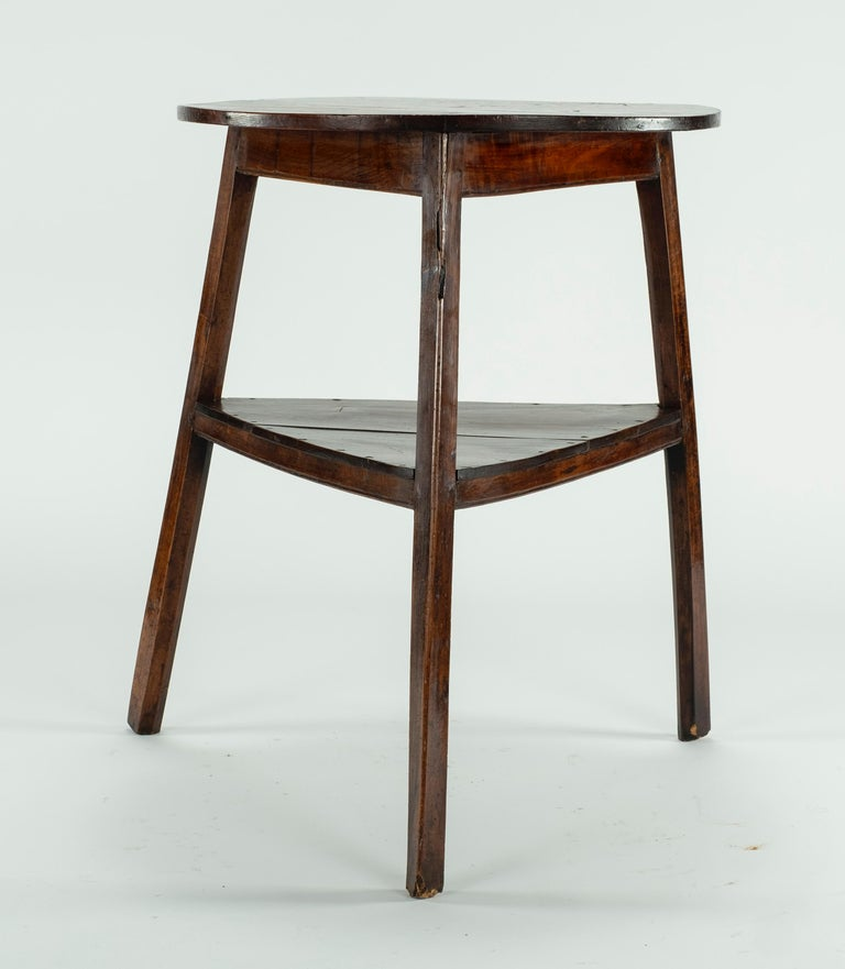 An early 19th century elm and fruitwood high cricket table. The round top on slightly splayed and chamfered legs united by a plank triangular under shelf.