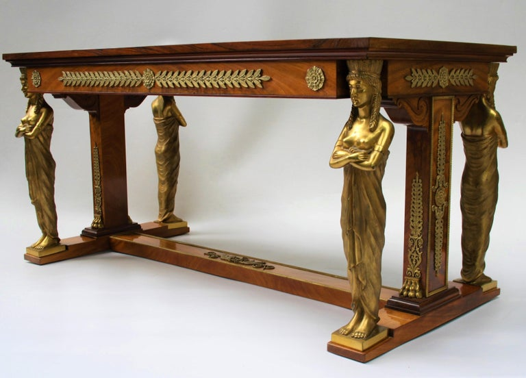 Exceptional 19th century Empire style desk after a design from Jacob-Desmalter Made of flamed mahogany supported on the heads of four finely cast gilt bronze female caryatids, and richly decorated with beautiful bronze fittings and black leather
