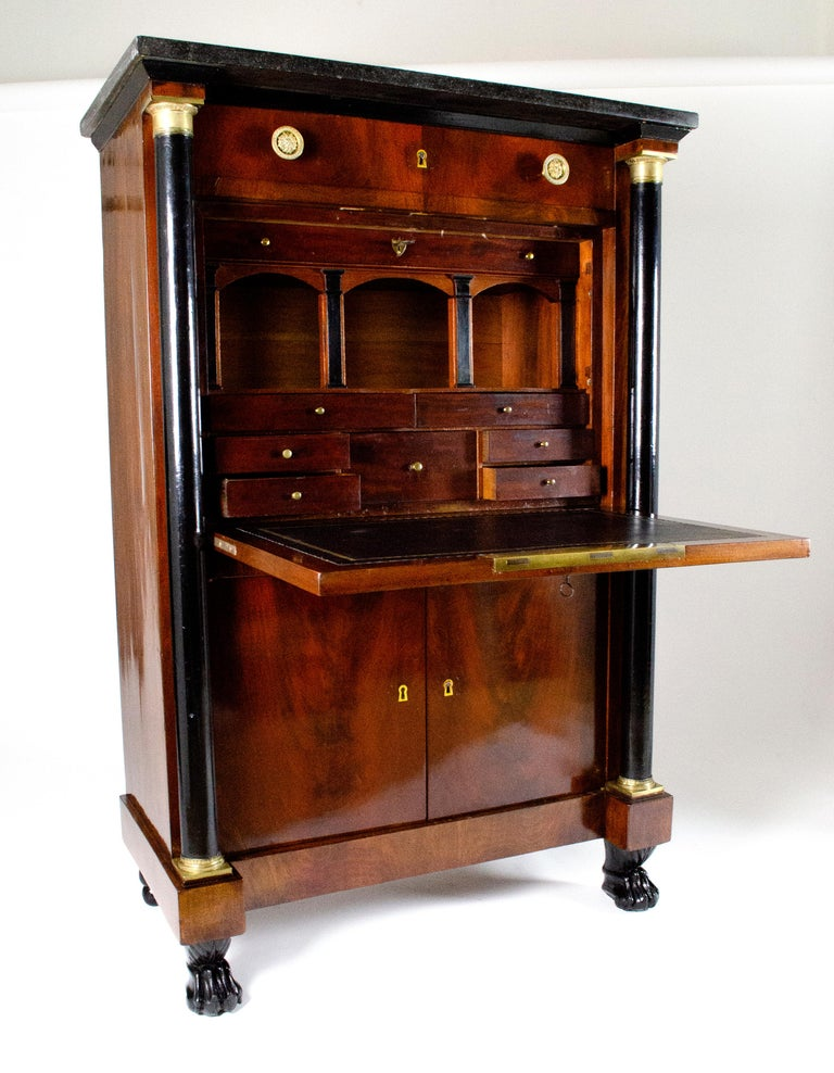 This secrétaire is from France from circa 1810. It is entirely made with mahogany wood and presents original marble, hardware and keys. The upper drop-front door hides many small drawers and a arch structure very particular. Here each arch is banded
