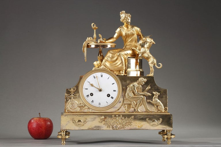 Early 19th century Empire clock crafted of gilt bronze, or ormolu, featuring an allegorical scene with a woman sitting at her work table playing with her dog, symbol of loyalty. The group is set above a raised case containing the dial. On one side