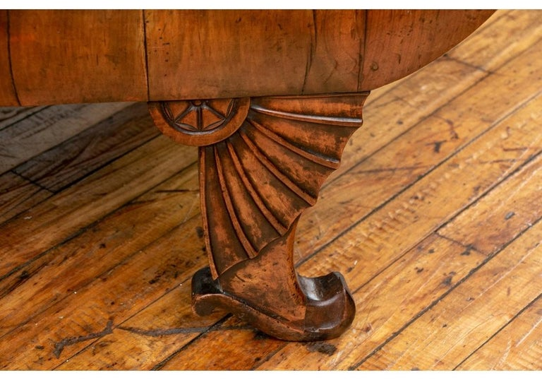 With a Classic Empire shaped crest rail and U-shaped frame with tall arms. The tops of the arms with carved leafy capitals. The front legs with fine carved fans with half rosettes ending in short curved and shaped feet. The back legs curved and