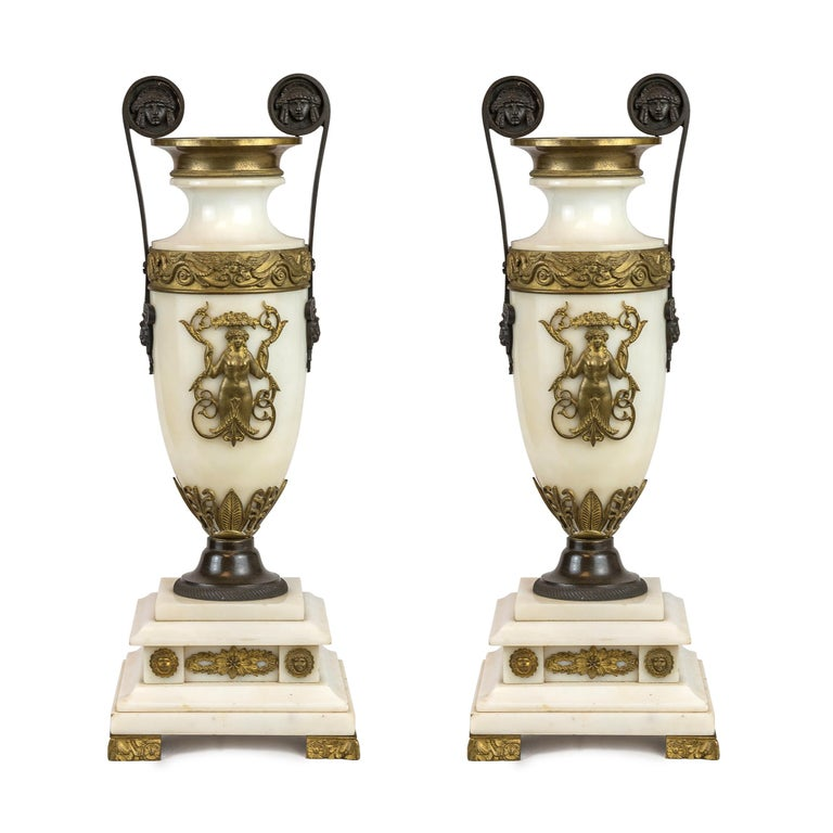 A Luxurious 19th century Empire style ormolu and white marble lyre clock garniture clockset. Known as a lyre clock for its graceful shape, this elegant piece is crafted with white marble and luxurious ormolu acanthus leaf and scroll in the