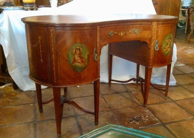 Superb quality, embellished with fine classic paintings. Very nicely detailed with elaborate twin cross stretches and appointed with a lather top. The drawer is finished with dust liners. Desirable kidney form.