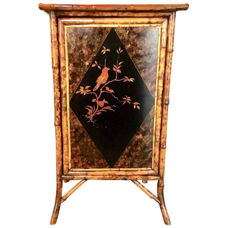 Lovely 19th century English bamboo cabinet with chinoiserie panels on three sides and the top. Beautiful motif's of birds and floral lacquered panels on all three sides and top. The inside has three areas with shelves in between. A great focal