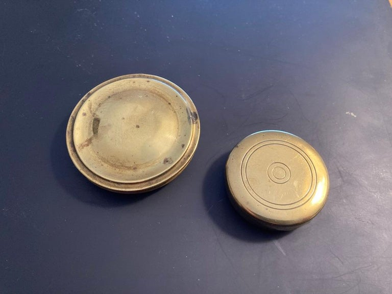 Two English brass pocket box compasses, both with handcrafted cases. The larger with beveled and beaded edges early 19th century. The smaller with incised circular decoration on top, late 18th-early 19th century. Each a little bit of