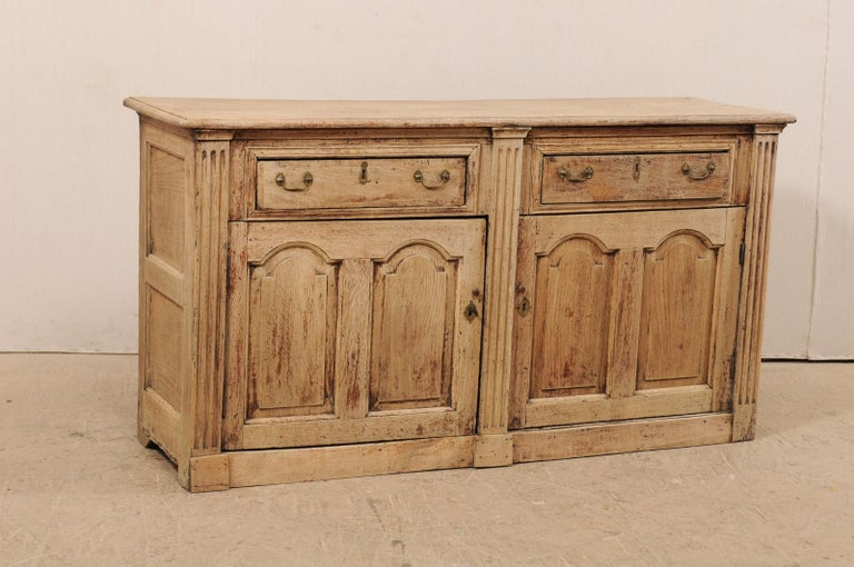 A 19th century English carved wood buffet cabinet with fluted columns. This antique cabinet from England, which is approximately 5.5 feet in length, features a slightly overhung rectangular-shaped top which rests atop a case having two half-drawers