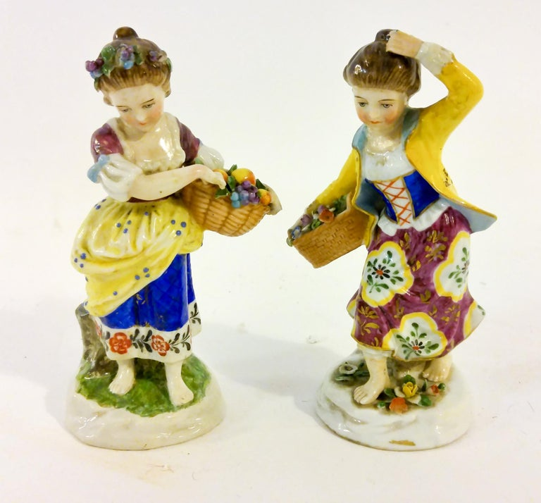 Charming pair of very intricate figurines of barefoot young girls, one gathering a basket of fruit and the other flowers. Only one is marked (with the gold anchor.) The colors are very brilliant and the details are incredible.