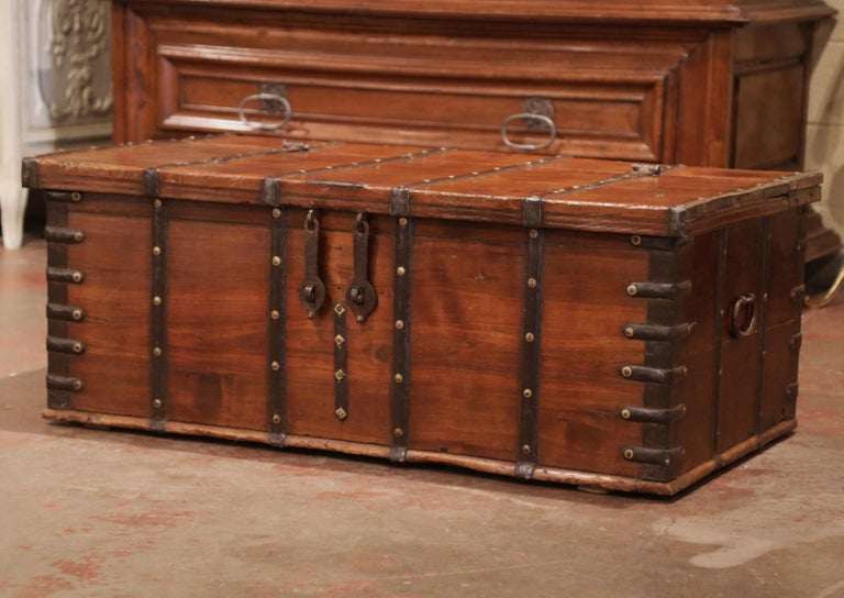 This large antique fruitwood coffee table trunk was crafted in England, circa 1870. The wooden blanket chest is finished on all four sides, and is decorated with metal strapping with decorative brass nail heads; it is further embellished with