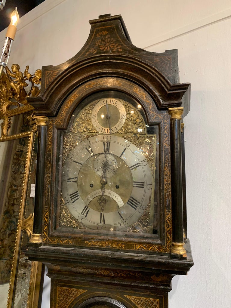 Beautiful 19th century English chinoiserie tall case clock. Lovely painted images on the piece and the face of the clock has a very pretty scrolling brass design.