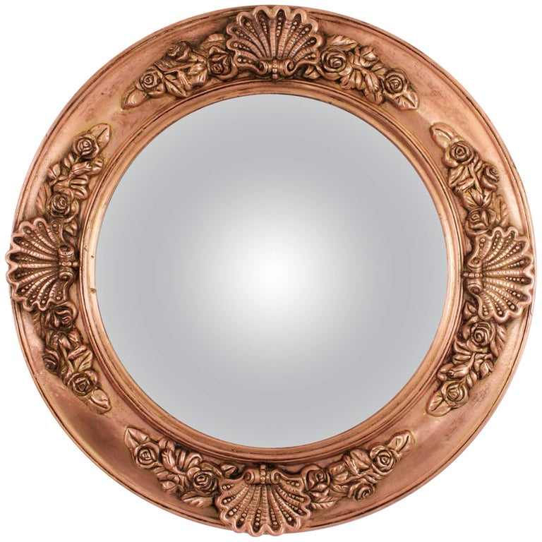 19th century English Regency molded copper circular convex mirror with shell motifs. England, 1820. A gorgeous Regency period copper circular convex mirror made of wood covered with copper relief molded flowers frame. This highly decorative mirror
