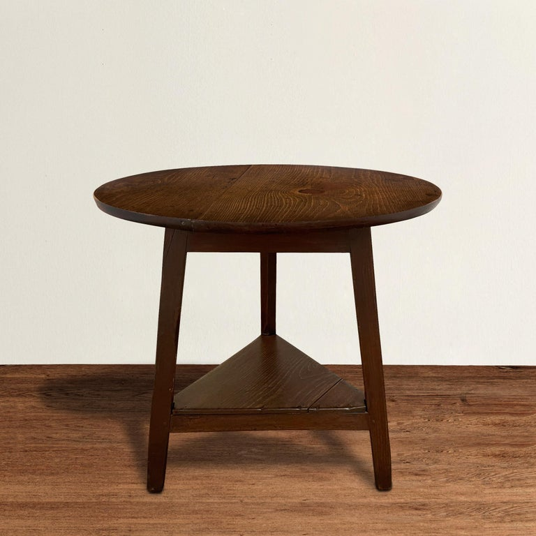 A charming 19th century English pine cricket table with clean lines, including three gently tapered legs pegged to a square apron, a shelf at the bottom, and a round top with a beautiful well-worn finish. Cricket tables were used in pubs and
