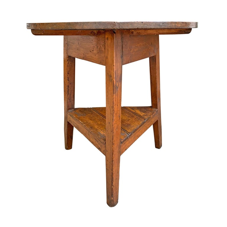 A fantastic 19th century English pine cricket table with three legs, a round top constructed of two pieces of wood, and a bead-board shelf on the bottom. Fantastic color!
