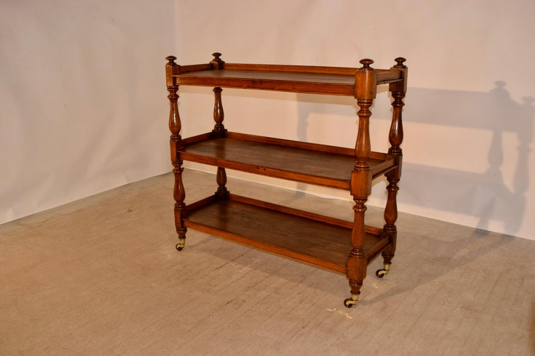 19th century oak dumbwaiter from England with three shelves, all with galleries and hand turned shelf supports. Supported on original brass casters. Staining on shelves due to age and use.