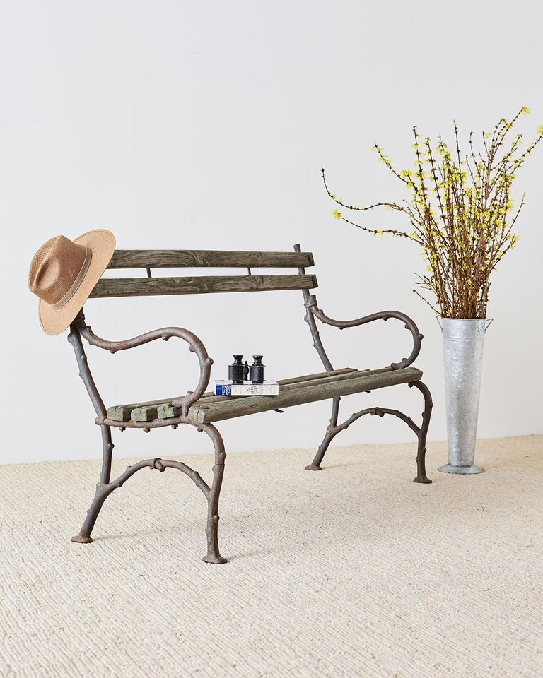 Rustic 19th century English garden bench having a branch twig style faux bois frame made of cast iron. The bench has graceful curved arms and legs with beautiful distressed patina on the cast iron and wood slats. Lovely understated style with a