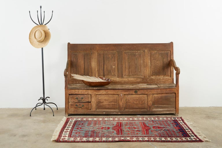 Rustic 19th century English Georgian box settle or hall bench. Crafted from oak featuring a paneled back. The large storage box has two small storage drawers on the front left with iron pulls. The seat has a hinged lid that opens to the large