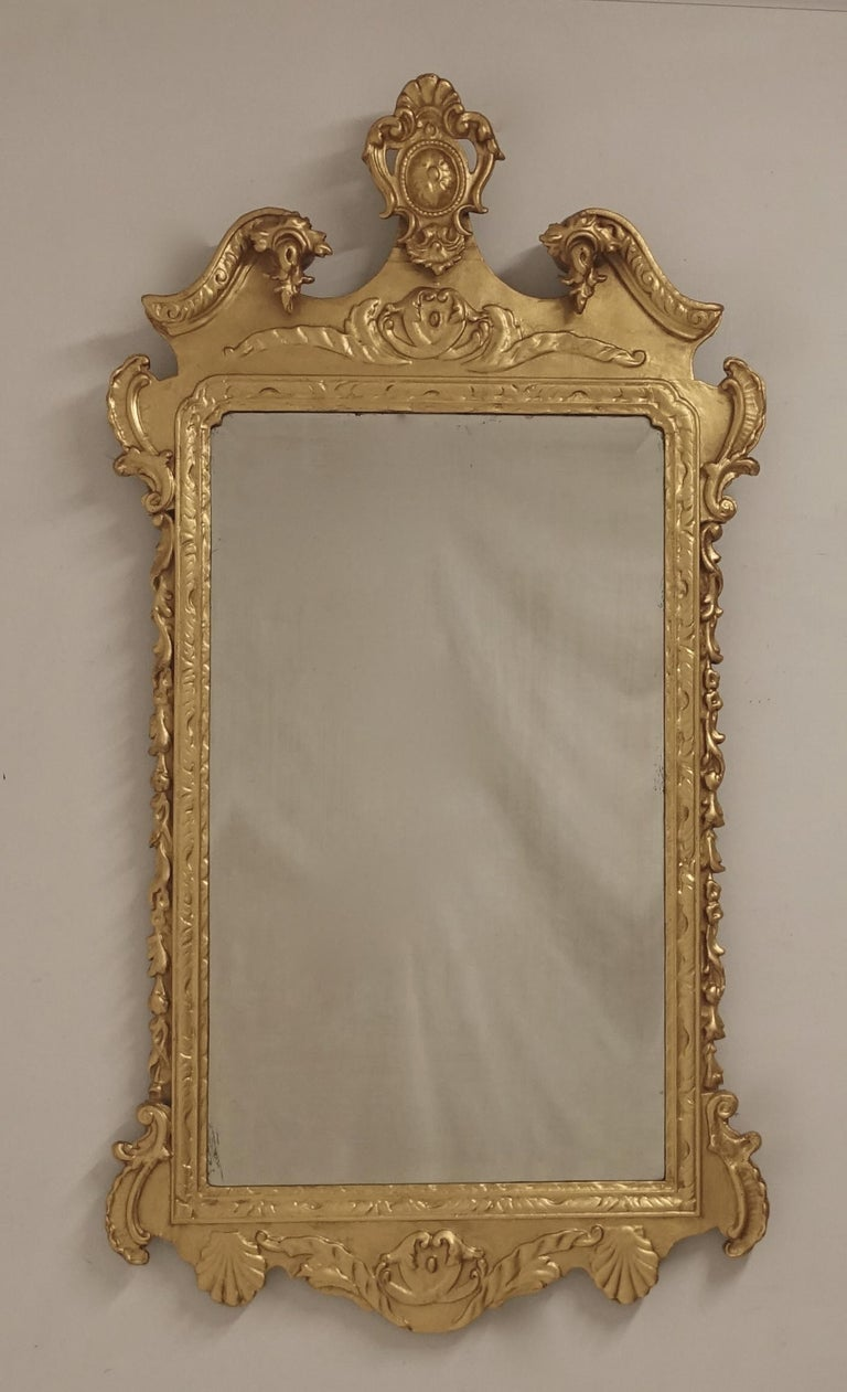 Mid-19th century English gilt wood wall or over mantle mirror in the Georgian style with original mirror plate. Gilding refreshed in the 20th century. In very good antique condition.