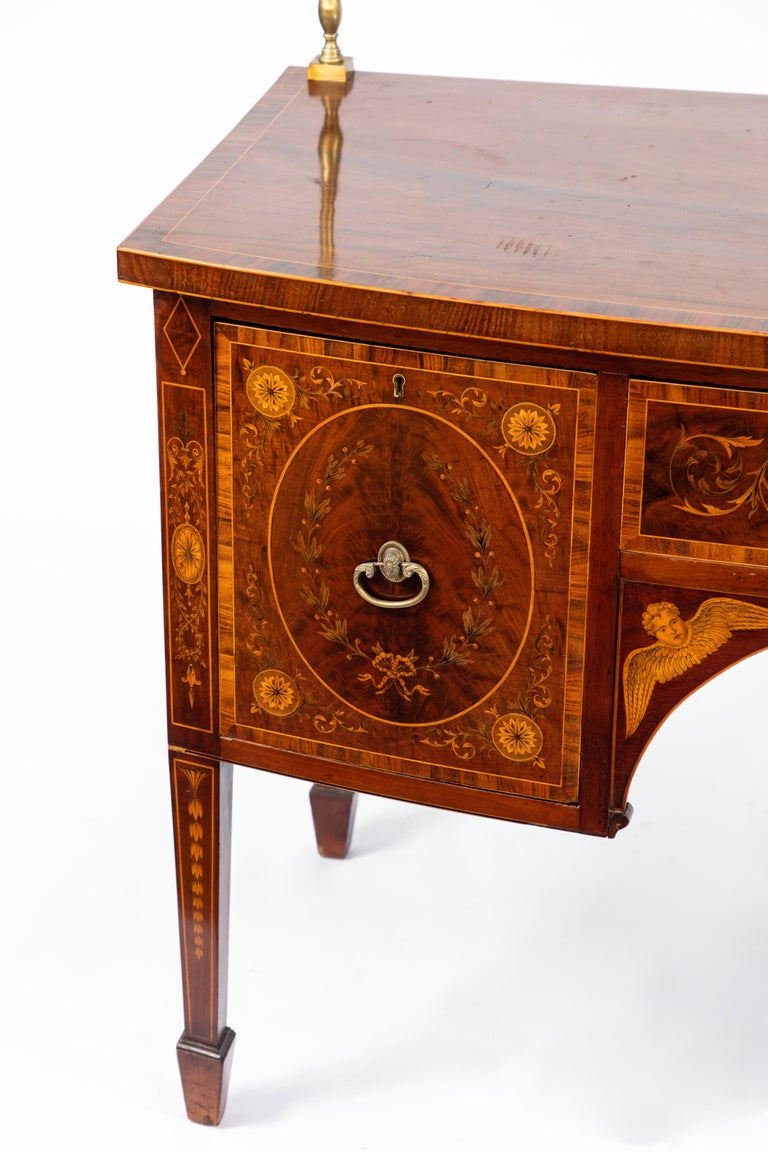 19th century English inlaid sideboard with very fine details of cherubs, rosettes etc. Original brass. Mahogany with satinwood inlay. Signed by the maker, London.