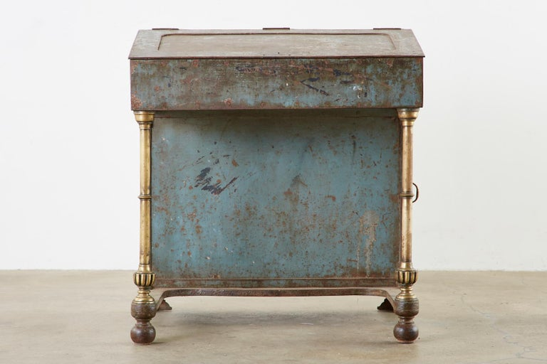 Rare 19th century English Industrial period davenport desk. Made from thick iron with bronze legs and campaign style handles on the drawers. The locking slant lid opens to reveal a large storage area with pigeon holes and two storage drawers. The