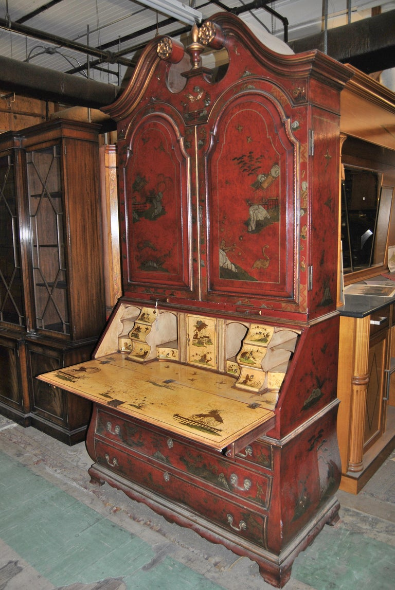 This is a lacquered gilt chinoiserie bookcase secretary or desk made in England, circa 1830. There is a fabulously shaped, deeply molded crown molding with hand carved rosetts and a nicely turned finial to the middle of the top. The pair of raised