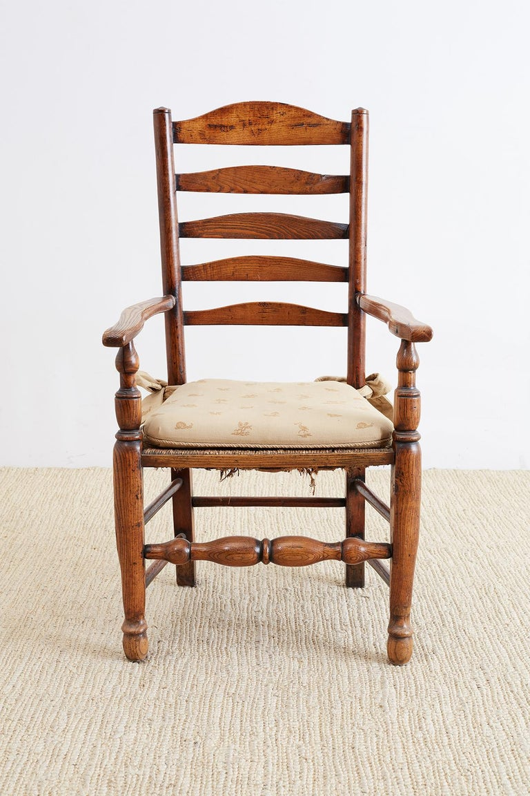 Large 19th century English carved oak armchair featuring a ladder back design and a rush seat. Sits on massive turned legs with box stretching. Wide elbow chair arms and a warm, rich patina on the vintage wood. From the Pebble Beach, California