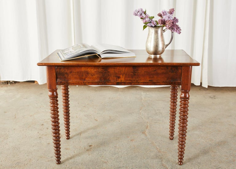 Handsome 19th century English console table, work table, or writing table made in the George IV taste. Constructed from radiant grained mahogany featuring elegant, tapered bobbin-turned legs. The case has a mahogany veneered front frieze with a