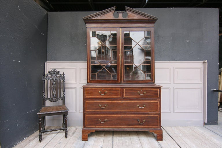 An 19th century English bookcase made with mahogany veneer and satinwood inlays. Consisting of a chest of drawers with 2 large and 2 small drawers, as well as the display case with 2 doors and a broken pediment on top.   Dimensions: 85 or 218 cm