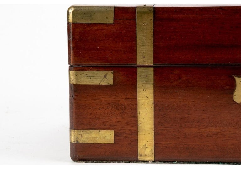 19th century English campaign travel lap desk. Rectangular form constructed out of mahogany with corner and banded brass accenting. Central inlaid brass crest. Top lifts open to reveal a velvet lined top that folds down to reveal a folio folder. The