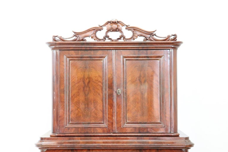 Antique English chest of drawers 1850s in mahogany wood. Very linear and essential with four comfortable drawers. On the front drawers with a particular rounded shape. Above the drawers a comfortable space with two doors. Refined decorative carving
