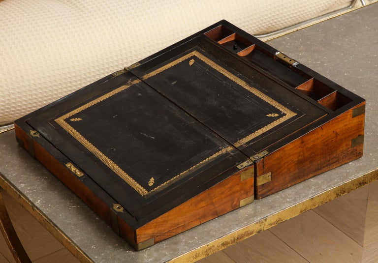 19th century English military Campaign portable mahogany writing box with brass bound molded edges and brass banding. Black leather writing slope with gold edge details and the rear half opens for storage. Unmarked brass plate on top.   When full
