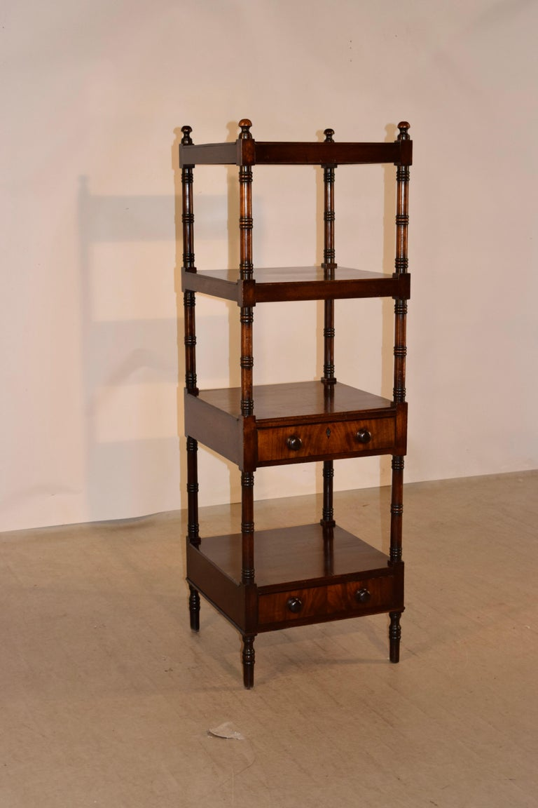 19th century mahogany shelf from England with finials decorating the top and four shelves, all separated by hand turned shelf supports. The two lower shelves have single drawers beneath, which is an unusual feature. The piece is raised on hand