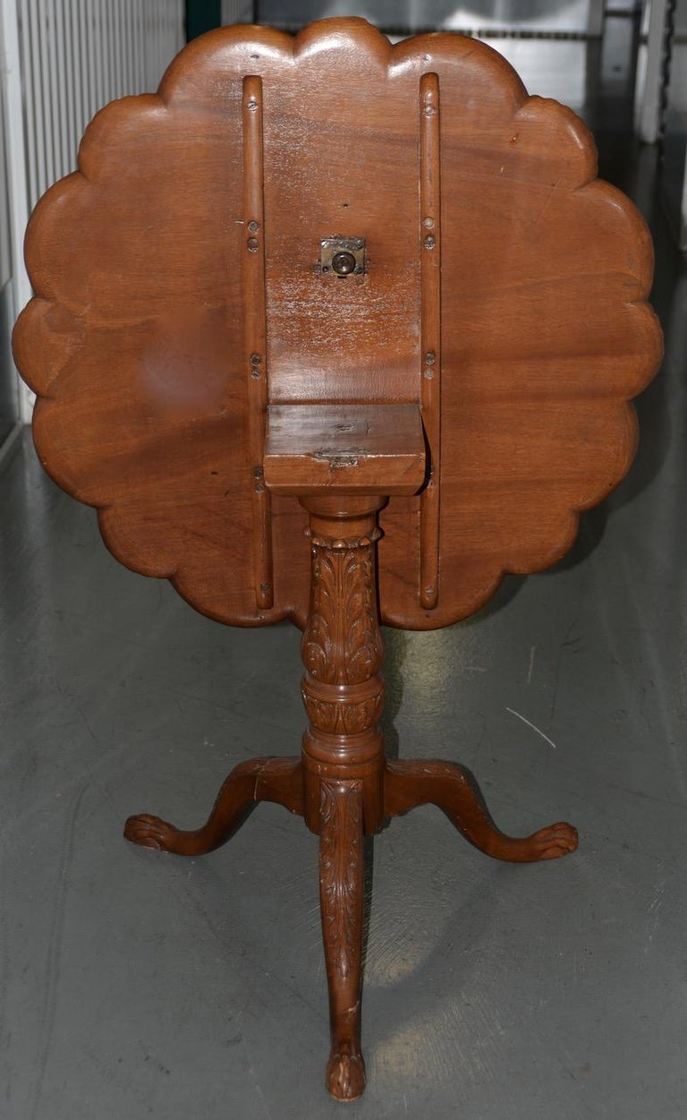 19th century English mahogany tilt-top serving table  Fantastic tilt-top serving table made from solid mahogany. Hand carved and custom made. Sitting atop a hand carved pedestal base.  The table is in remarkably good condition for piece of