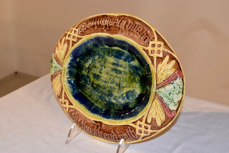 19th century majolica bread tray from England with a multi colored central medallion in blue and green, surrounded by a lovely molded border in yellow, pink, green and blue with designs of wheat and geometric designs encircling the words