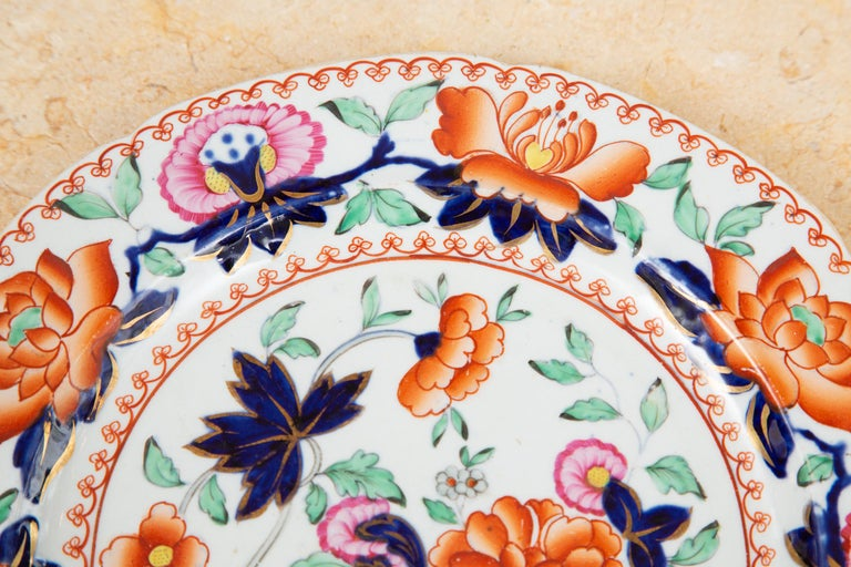 This is a very collectible set of English Mason's ironstone plates, depicting a Chinese urn centered among a colorful display of flowers and foliage hand painted in corals, melons, cobalts and greens. 19th century. The plates are prices individually.