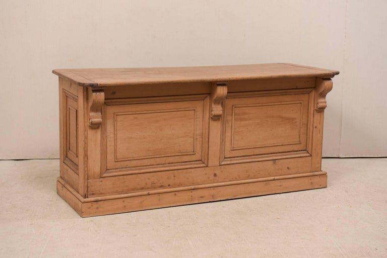An English kitchen island from the 19th century. This antique natural finished wooden island features a rectangular-shaped overhanging top (at one long side) supported with three large carved volute brackets, with recessed panels decorating the