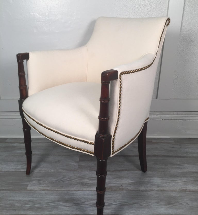 And antique English Regency style mahogany upholstered armchair with brass nailhead trim and Classic Regency faux bamboo carved legs. The newly covered chair in a white cotton duck cloth in excellent condition.