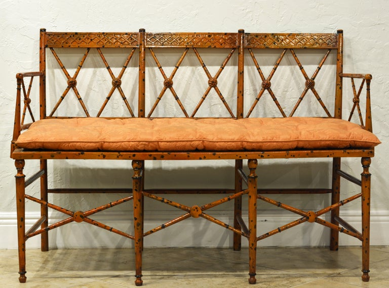 Fashioned in the Regency stylized bamboo style this settee is charmingly painted in a warm honey color with darker spots simulating bamboo. The cane seat is reinforced by a firm panel and comes with a very nice cushion in good condition.
