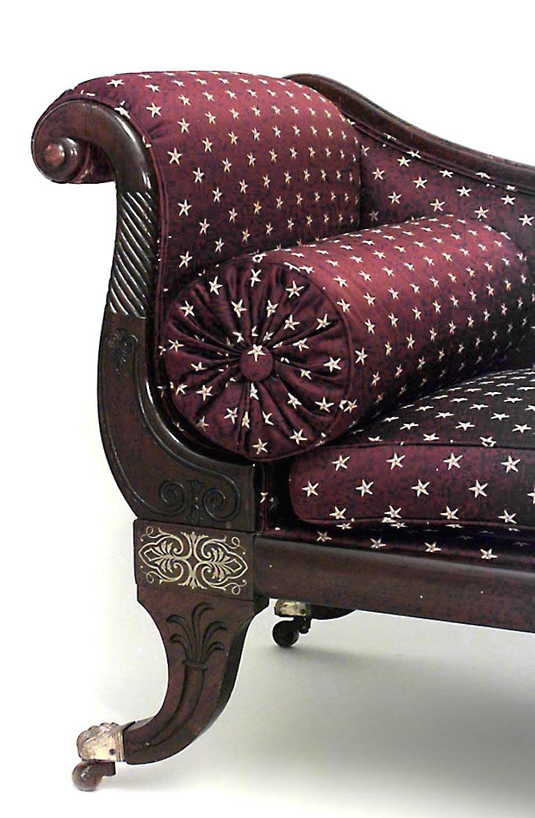 Nineteenth century English Regency style roll arm recamier composed of mahogany decorated with carved and inlaid brass designs along its frame. The recamier is upholstered in maroon fabric decorated with gold stars.