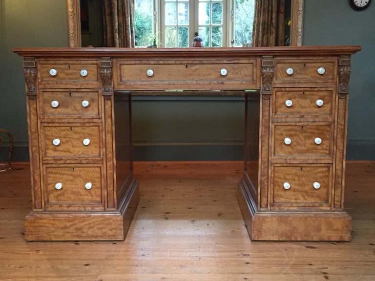 An exquisite 19th century pedestal desk in satinwood, the original tooled leather top over a central frieze drawer; each pedestal with carved corbels, four graduated drawers all with their original handles and plinth bases. This desk is in one