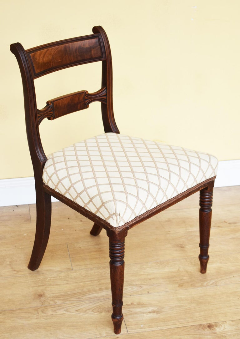 For sale is a good quality set of 8 Regency mahogany dining chairs, each with horizontal bar back and silk stuffover seats, standing on turned legs. All of the chairs are in good condition, being structurally sound and having only minor wear