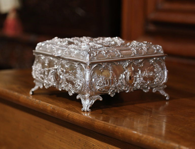 Place this elegant antique silver coated copper box in your master bath to keep your jewelry safe and organized. Crafted in England circa 1880, the ornate square casket sits on four scroll feet and has four bow sides embossed with foliage decor, and