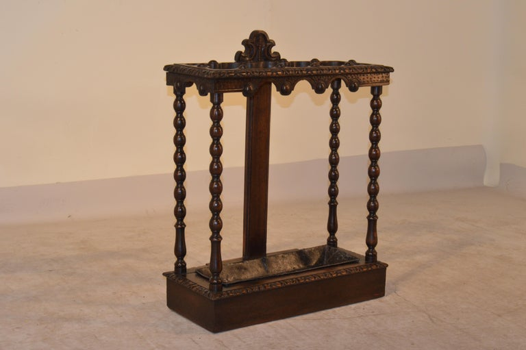 19th century English oak umbrella stand with a heavily carved top which is scalloped in sections for umbrella or cane storage. The apron is scalloped and carved to match. The legs are hand-turned in a spool design. The base is banded and has a